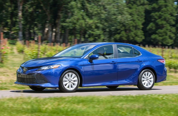 2018 Toyota Camry in blue driving down a road