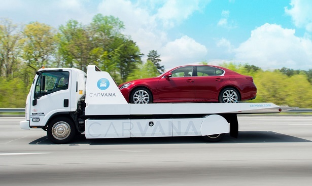 carvana car transport flatbed driving with red lexus gs