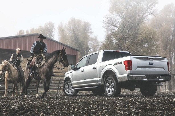 2018 ford f-150 next to two cowboys on horses