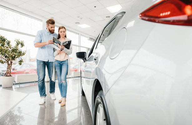 couple shopping for a new car while looking at a magazine