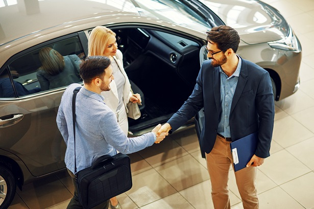 couple shaking hands with car seller
