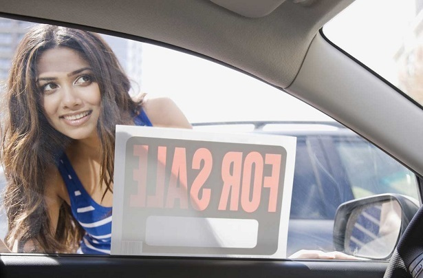 woman looking through car window with for sale sign