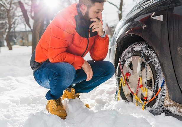 Man looking at tire chains