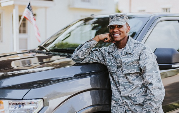 soldier leaning on hood of SUV